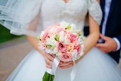 Marié de prise de jeune mariée par le bouquet de main et de mariage Foyer sur le weddi Photographie stock libre de droits