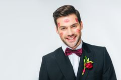 Marié de sourire beau dans le costume avec le rouge à lèvres rouge sur le visage Photographie stock libre de droits