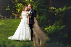 Marié embrassant la jeune mariée près de la barrière en bois Photographie stock