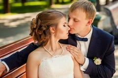 Marié embrassant la jeune mariée sur le portrait de banc Images stock