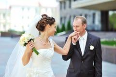 Marié embrassant la main de la jeune mariée tout en marchant ensemble Photos libres de droits