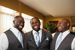 Marié et garçons d'honneur souriant à un mariage images stock