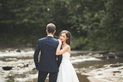 Marié et jeune mariée élégants doux élégants près de rivière avec des pierres Couples de mariage dans l'amour Photographie stock