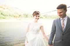 Marié et jeune mariée élégants doux élégants près de rivière avec des pierres Couples de mariage dans l'amour Photo libre de droits