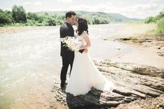 Marié et jeune mariée élégants doux élégants près de rivière avec des pierres Couples de mariage dans l'amour Photographie stock libre de droits