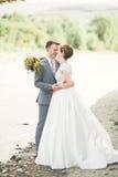 Marié et jeune mariée élégants doux élégants près de rivière avec des pierres Couples de mariage dans l'amour Images libres de droits