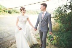 Marié et jeune mariée élégants doux élégants près de rivière avec des pierres Couples de mariage dans l'amour Photo stock