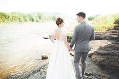 Marié et jeune mariée élégants doux élégants près de rivière avec des pierres Couples de mariage dans l'amour Image libre de droits