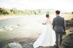 Marié et jeune mariée élégants doux élégants près de rivière avec des pierres Couples de mariage dans l'amour Photos libres de droits