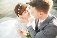 Marié et jeune mariée élégants doux élégants près de rivière avec des pierres Couples de mariage dans l'amour Photos stock