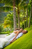 Marié et jeune mariée étreignant sur une herbe verte sur un fond des palmiers photos libres de droits