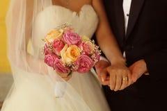 Marié et jeune mariée avec le bouquet de mariage Images stock