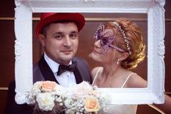 Marié et jeune mariée dans un cadre blanc Photographie stock libre de droits