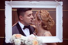 Marié et jeune mariée dans un cadre blanc Images stock