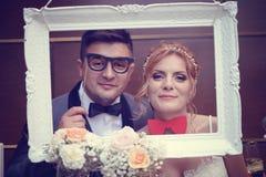 Marié et jeune mariée dans un cadre blanc Photos libres de droits