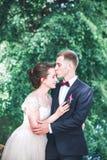 Marié et jeune mariée ensemble Accouplez étreindre Jour du mariage Belle jeune mariée et marié élégant marchant après cérémonie d Image libre de droits