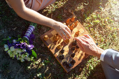 Marié et jeune mariée ensemble le jour du mariage jouant des échecs et démontrant des anneaux Photo stock