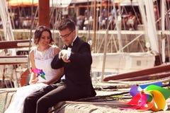 Marié et jeune mariée jouant avec le propulseur de moulin à vent Photos stock