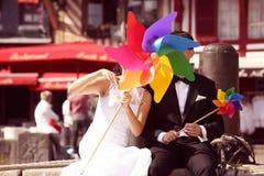 Marié et jeune mariée jouant avec le propulseur de moulin à vent Images libres de droits