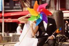 Marié et jeune mariée jouant avec le propulseur de moulin à vent Image stock
