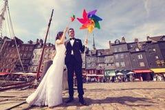 Marié et jeune mariée jouant avec le propulseur de moulin à vent Photos libres de droits