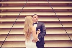Marié et jeune mariée posant près d'un mur dépouillé Photo libre de droits