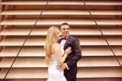 Marié et jeune mariée près d'un mur dépouillé Photographie stock libre de droits
