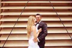 Marié et jeune mariée près d'un mur dépouillé Photographie stock