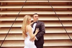 Marié et jeune mariée près d'un mur dépouillé Image stock