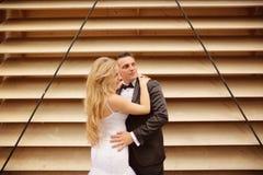 Marié et jeune mariée près d'un mur dépouillé Image libre de droits