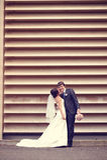 Marié et jeune mariée près d'un mur dépouillé Photos stock