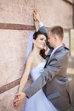Marié et jeune mariée près de mur Photographie stock libre de droits