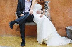 Marié et jeune mariée s'asseyant sur un banc Image libre de droits
