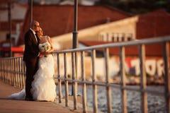Marié et jeune mariée sur un pont près de la mer Photographie stock libre de droits