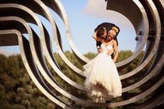 Marié et jeune mariée sur une grande construction métallique Images stock