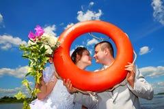 Wedding.Groom et jeune mariée avec un lifebuoy Images stock