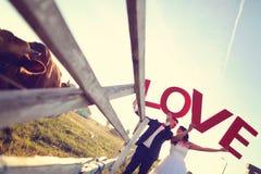 marié et jeune mariée tenant des lettres d'AMOUR Photos libres de droits