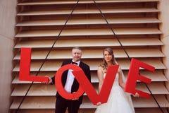 marié et jeune mariée tenant des lettres d'AMOUR Image stock