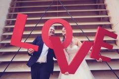 marié et jeune mariée tenant des lettres d'AMOUR Image libre de droits