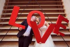 marié et jeune mariée tenant des lettres d'AMOUR Photographie stock
