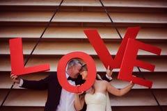 marié et jeune mariée tenant des lettres d'AMOUR Images stock