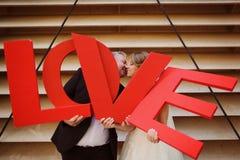 marié et jeune mariée tenant des lettres d'AMOUR Photo stock