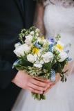 Marié et jeune mariée tenant un bouquet de mariage en parc, plan rapproché, Photographie stock libre de droits