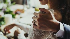 Marié Hand Holding Bride étroitement sur la réception de mariage Photo libre de droits