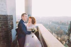 Marié heureux embrassant sa belle nouvelle épouse sur le balcon de la vieille cathédrale gothique Image libre de droits
