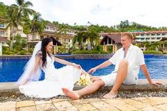 Marié heureux et jeune mariée s'asseyant par la piscine Mariage et lune de miel Images stock