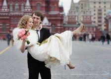 Marié heureux tenant la belle jeune mariée Images stock