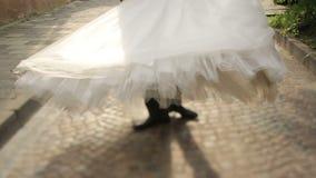 Marié heureux tournant sa belle jeune mariée blonde devant une église chrétienne antique à Lviv clips vidéos