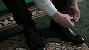 Marié mettant ses chaussures de mariage Les mains du mariage toilettent être prêtes dans le costume clips vidéos