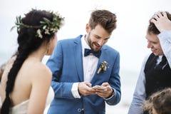 Marié occupé avec le téléphone à la cérémonie de mariage de plage image libre de droits